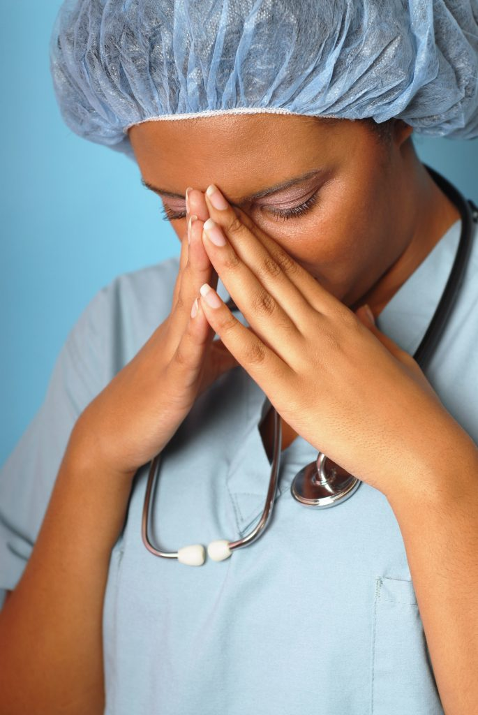 Crying nurse with her hands on her face